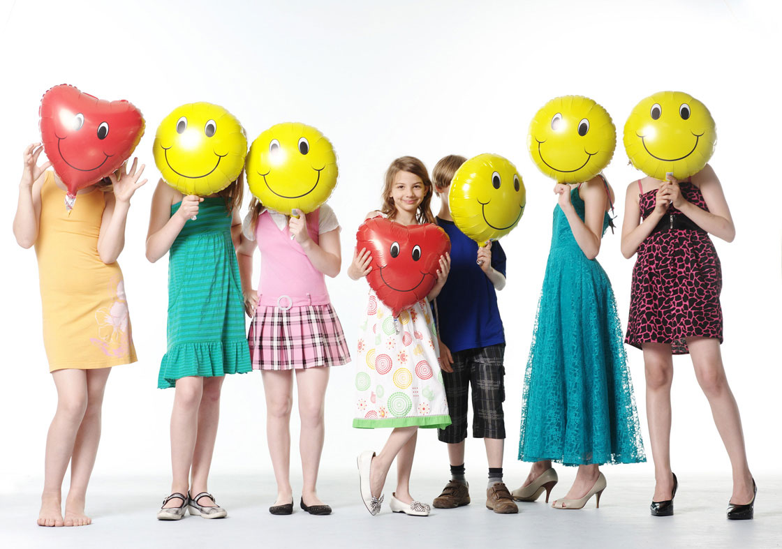 Kinder Smiley Luftballons vor Gesicht